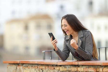 Mujer emocionada comprobando el teléfono inteligente en un balcón con una ciudad al fondo Foto de archivo