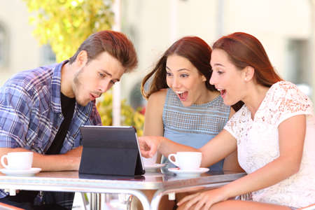 Three excited friends watching tablet content sitting in a coffee shop