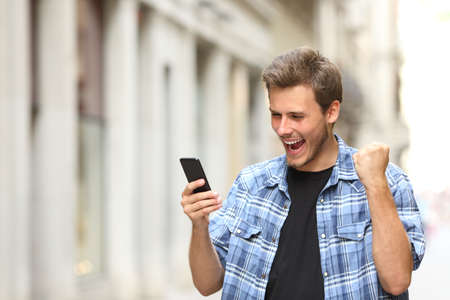 Excited man checking news on smart phone walking in the street Stock Photo
