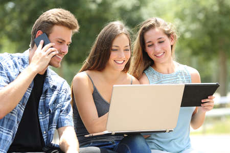 Three happy friends using multiple devices sitting on a bench in a park