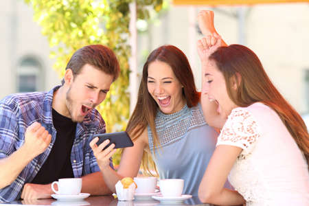 Three excited friends celebrating good news watching smart phone media content in a coffee shop Фото со стока