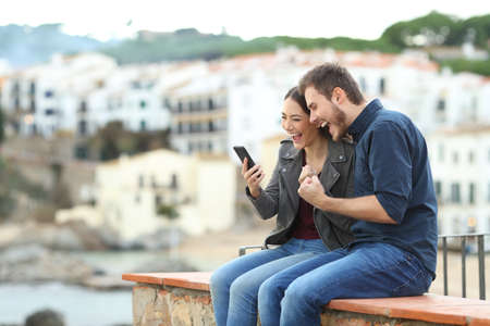 Excited couple finding news on smart phone on a ledge with a town in the background
