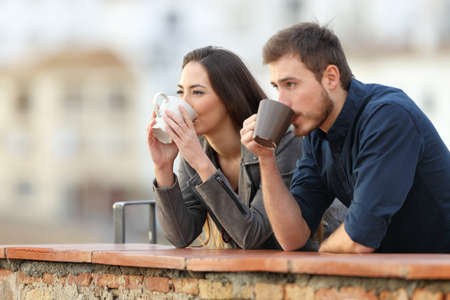 Happy couple drinking coffee watching views in a terrace Stock Photo