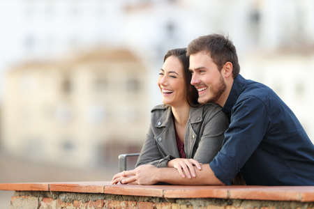 Happy couple enjoying views in a rural apartment terrace on vacation