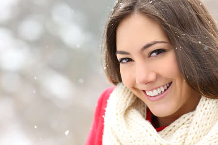 Beauty girl with perfect smile posing looking at camera in a snowy winter Stok Fotoğraf