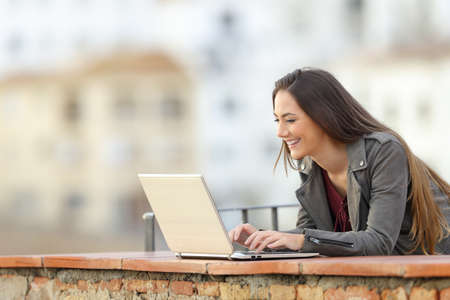 Happy woman using a laptop in a rural apartment terrace on vacation