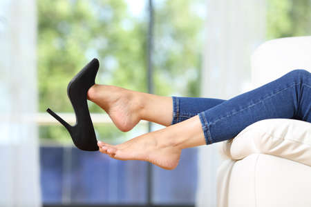 Side view close up of beautiful woman feet taking off shoes resting lying on a couch in the living room at home
