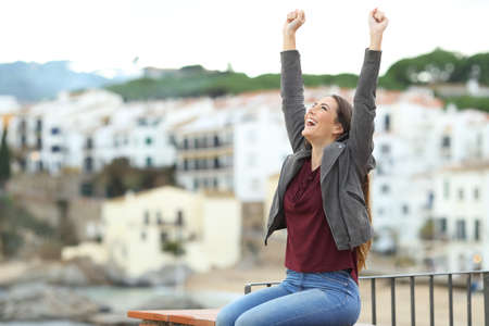 Excited girl celebrating vacation raising arms in a coast town Foto de archivo