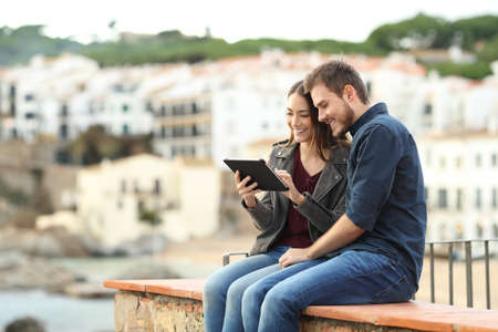 Happy couple sitting on a ledge using a tablet on vacation in a coast town