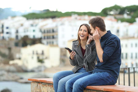 Happy couple sharing online music from a smart phone sitting on a ledge on vacation in a coast town