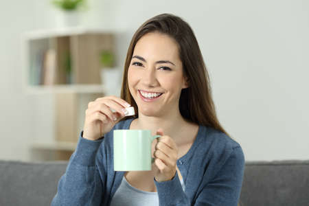 Happy woman throwing sugar into mug looking at you sitting on a couch in the living room at home