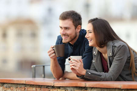 Happy couple on vacation drinking coffee looking away in a terrace