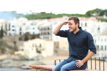 Happy man scouting sitting on a ledge in a coast town on vacation Stockfoto