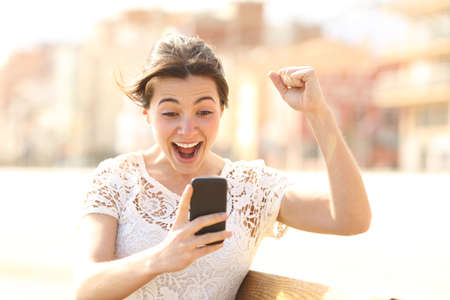 Excited woman reading amazing news on a smart phone sitting on a bench in the street