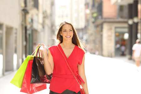 Front view portrait of a happy shopper walking towards camera holding shopping bags in the street of an old town Stock Photo
