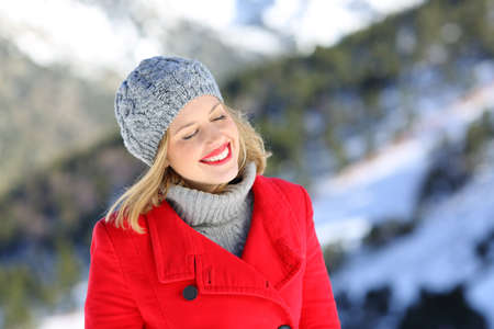 Happy woman in red with closed eyes enjoying winter holiday in the snowy mountain Stockfoto