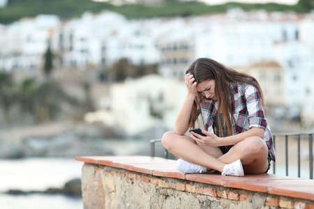 Sad teenage girl reading smart phone content sitting on a ledge in a coast town Stock Photo