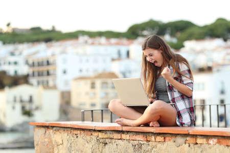 Emocionada adolescente comprobando el contenido de la computadora portátil sentado en una repisa en una ciudad costera de vacaciones