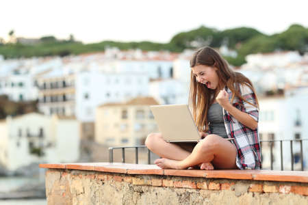 Excited teenage girl checking laptop content sitting on a ledge in a coast town on vacation Standard-Bild - 114106183