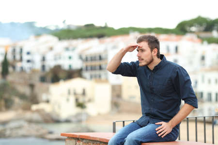 Serious man scouting sitting on a ledge on vacation in a coast town Stockfoto