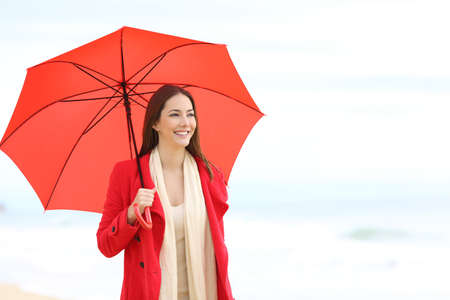 Happy woman in red holding an umbrella walking on the beach a rainy day
