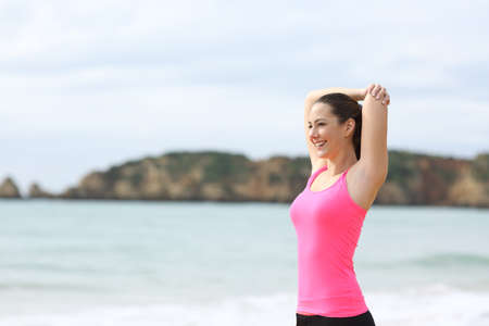 Sportswoman in pink stretching arms after sport on the beach Imagens