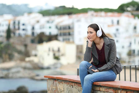 Sad woman listening to music sitting on a ledge in a coast town Stock Photo