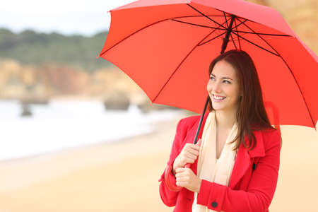 Happy woman in red holds an umbrella walking on the beach in a rainy day