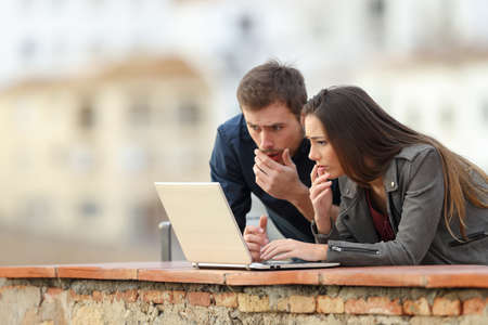 Worried couple checking bad news on a laptop in a rural apartment terrace on vacation Фото со стока