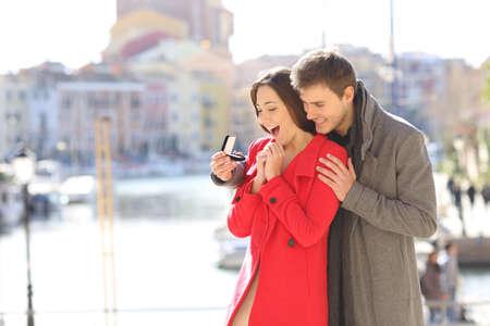 Novio feliz pidiendo casarse con su novia alegre en una ciudad costera en invierno Foto de archivo