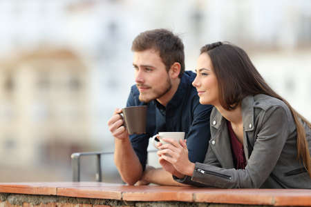 Happy couple relaxing drinking coffee in a balcony looking away on vacation 스톡 콘텐츠