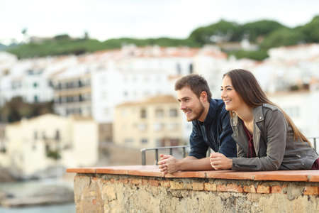 Happy couple contemplating views from a balcony on vacation in a coast town Imagens