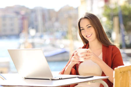 Happy woman with laptop holding a drink looking at you in a bar terrace Stock Photo
