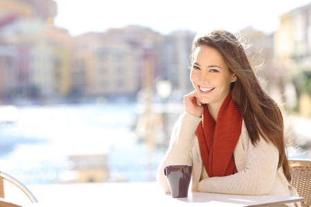 Happy woman looking at camera sitting in a coffee shop of a port of a coast town Foto de archivo - 115349972