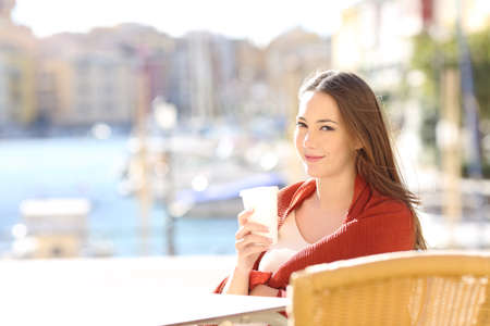 Confident woman on vacation posing looking at camera in a bar on vacation Foto de archivo - 115349975