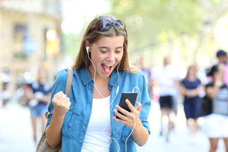 Excited girl listening to online music outdoors in the street