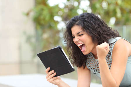 Excited girl holding a tablet and celebrating news on line in a park