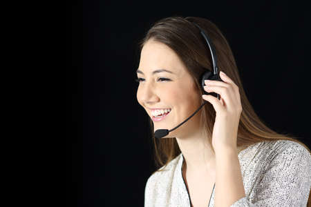 Portrait of a happy tele marketer attending call on black isolated background
