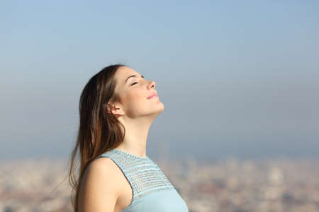 Happy woman breathing deep fresh air with a city in the background Stock Photo