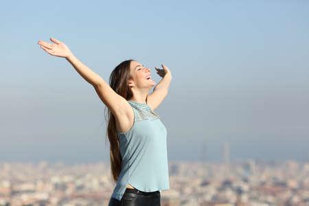 Donna eccitata che alza le braccia per celebrare le vacanze con una città sullo sfondo