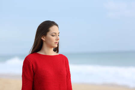 Melancholic woman in red walking alone on the beach Stock Photo - 115350153