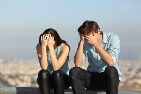 Sad couple complaining after argument sitting outdoors in a city ourskirts