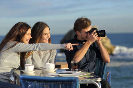 Three happy tourists taking photos from a coffee shop on the beach on vacation