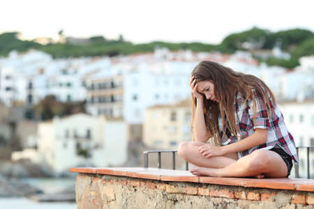 Sad teen complaining sitting on a ledge on vacation in a coast town Stock Photo
