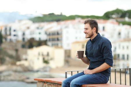 Happy man drinking coffee and looking away sitting on a ledge in a coast town on vacation Stockfoto