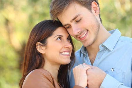 Feliz pareja de enamorados mirándose cogidos de la mano de pie en un parque