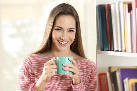 Front view portrait of a happy woman holding a coffee cup looks at camera