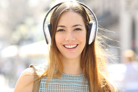 Front view portrait of a teenage girl wearing headphones listening to music looking at camera in the street Banque d'images - 115350246