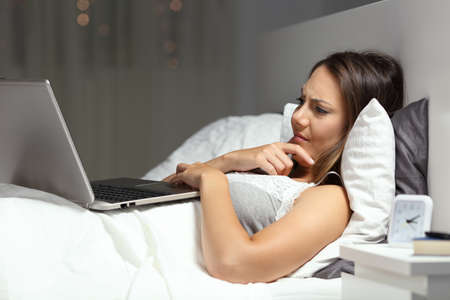Confused woman using a laptop lying on the bed in the night at home Stock Photo