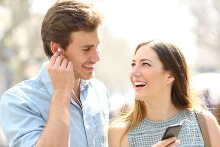 Happy romantic couple sharing online music dating in the street 版權商用圖片